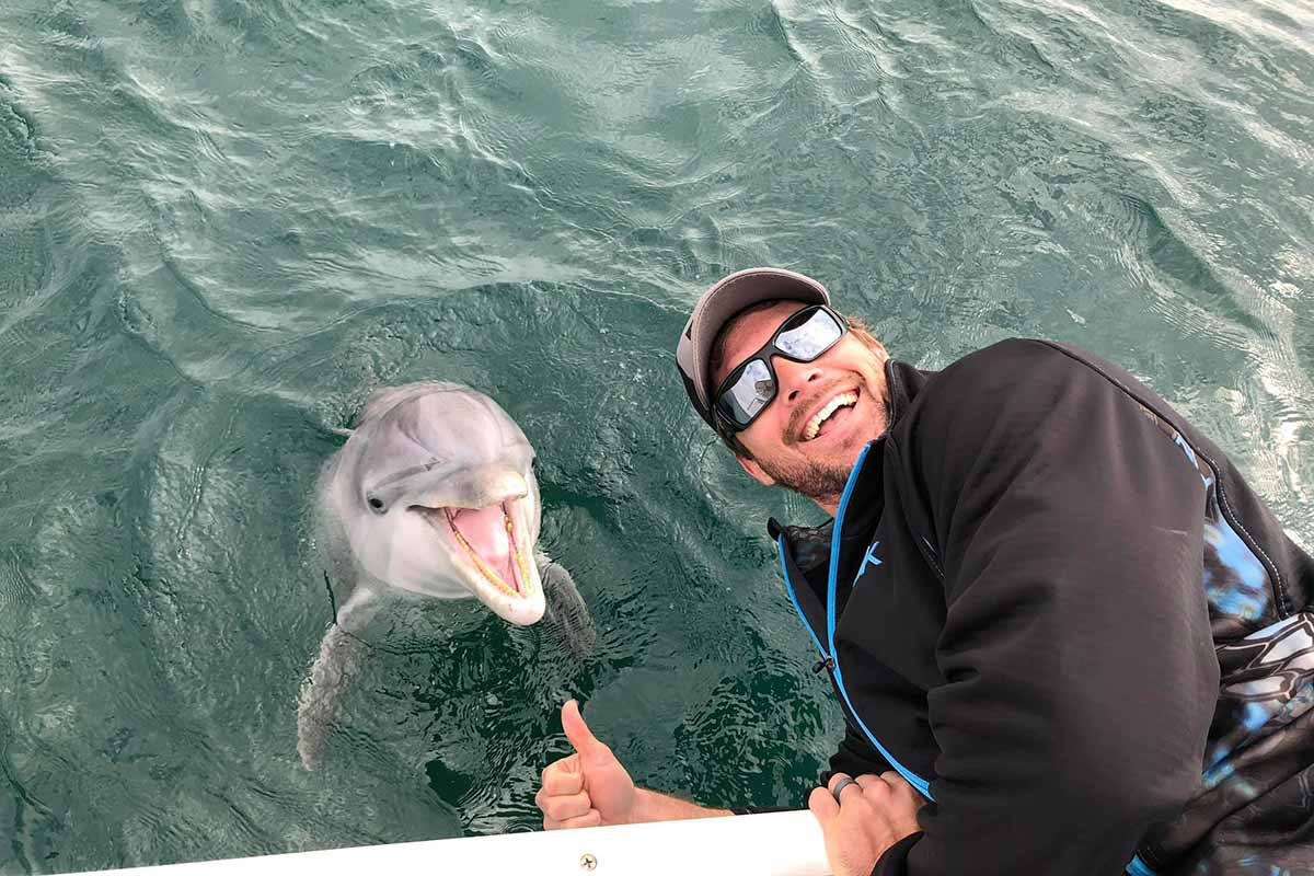 Man leaning over the edge of the boat to be near a dolphin the water. Both of them are smiling and looking at the camera